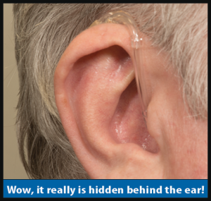 Image of a person wearing the HHE-33. It's practically hidden behind their ear.
